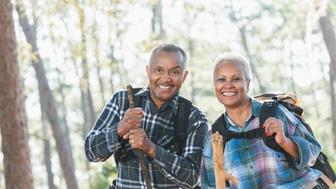 An African American senior couple hiking through the woods carrying backpacks and walking sticks. They are smiling, looking at the camera.