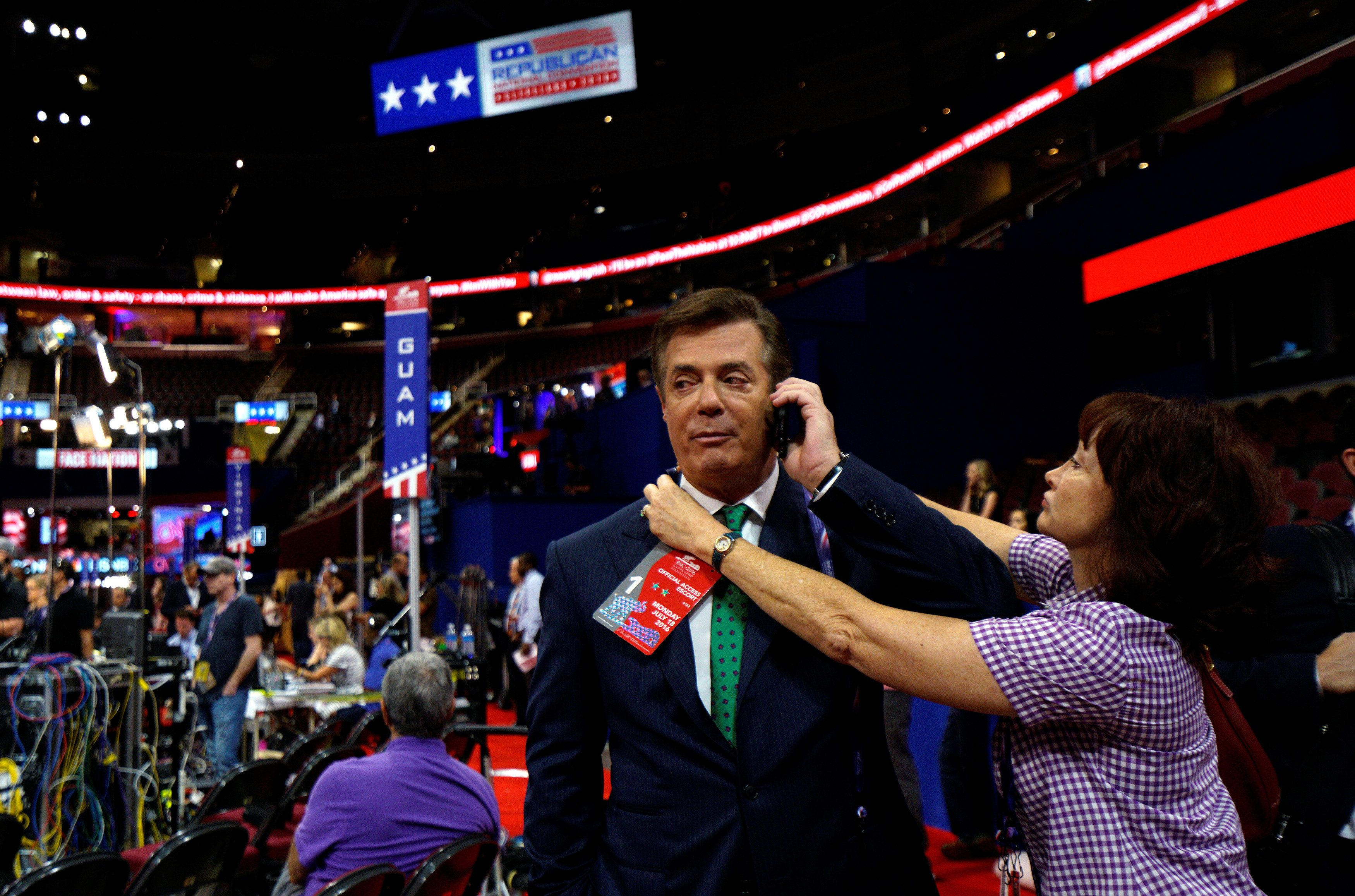 Kathleen Manafort tries to put a credential on her husband Paul Manafort, campaign manager to Republican Presidential Candidate Donald Trump, as he talks on the phone from the floor of the Republican National Convention in Cleveland, U.S., July 17, 2016.  REUTERS/Rick Wilking