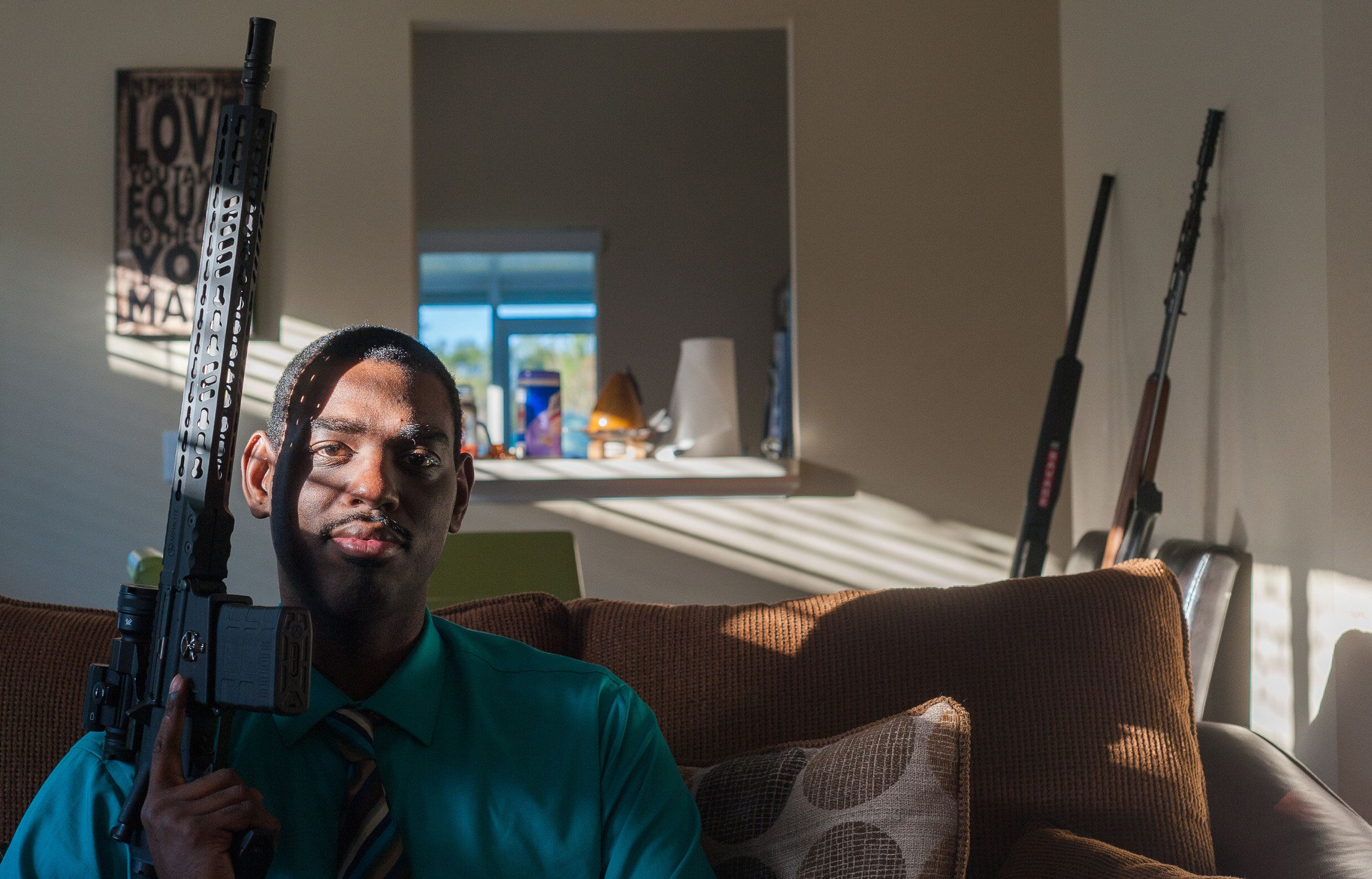 Carlton LeFlore poses with an Armalite AR-10 rifle at his home in Orlando, Florida.