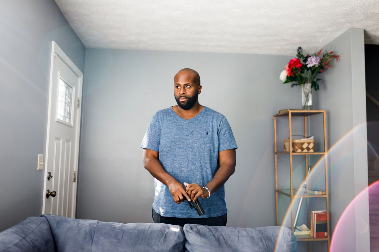 David White poses for a photo with his handgun in his home in Atlanta. He is a recent first-time gun owner.