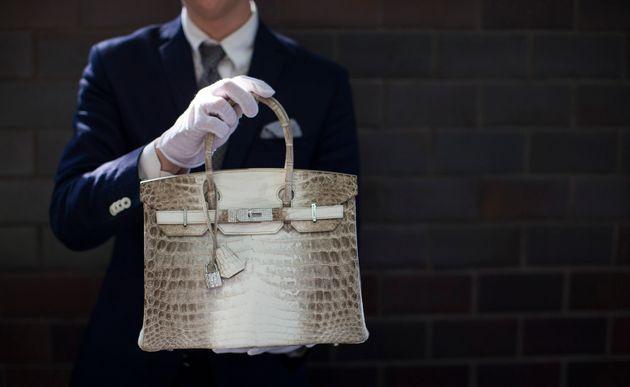 An employee holds an Hermes diamond and Himalayan Nilo Crocodile Birkin handbag at Heritage Auctions...