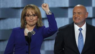 Former U.S. Representative Gabby Giffords, victim of a shooting attack while she was a member of Congress, pumps her fist as her husband, retired astronaut Mark Kelly, watches as she speaks on the third night at the Democratic National Convention in Philadelphia, Pennsylvania, U.S. July 27, 2016. REUTERS/Mike Segar