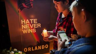 BEIJING, CHINA - JUNE 14: A Chinese man lights a candle at a memorial vigil for the victims of the mass shooting at the Pulse nightclub, at Adam's Bar on June 14, 2016 in Beijing, China. The mass shooting by a lone gunman at the gay club in Orlando, Florida killed at least 49 people and injured 53 others in what is the deadliest mass shooting in United States history. Adam's Bar is the first openly gay, lesbian, bisexual and transgender bar in China's capital. (Photo by Kevin Frayer/Getty Images)