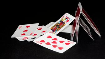 close shot of a fallen house of cards on black background