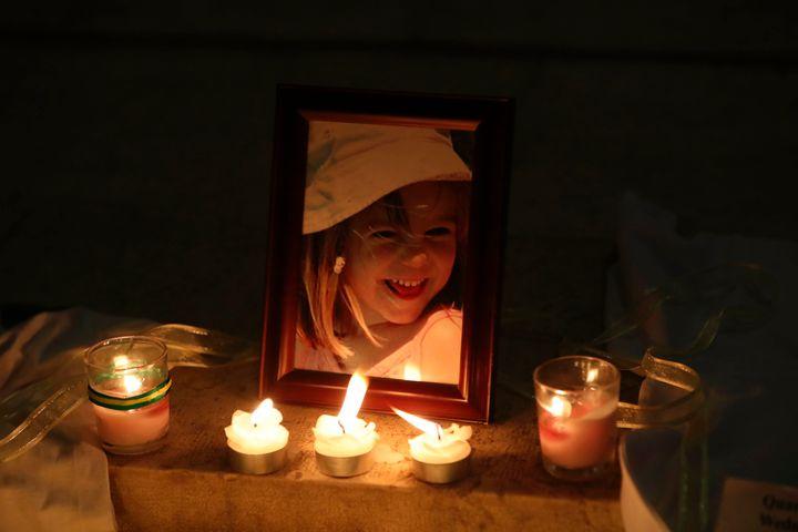 Candles light a photograph of Madeleine McCann inside the church of Praia da Luz, near Lagos, on May 3, 2017, during a mass c