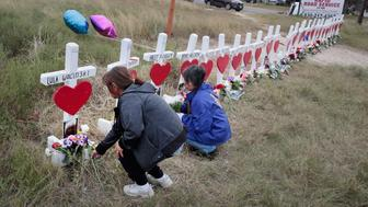 SUTHERLAND SPRINGS, TX - NOVEMBER 09:  Visitors leave flowers at a memorial where 26 crosses were placed to honor the 26 victims killed at the First Baptist Church of Sutherland Springs on November 9, 2017 in Sutherland Springs, Texas. On November 5, a gunman, Devin Patrick Kelley, shot and killed the 26 people and wounded 20 others when he opened fire during Sunday service at the church.  (Photo by Scott Olson/Getty Images)