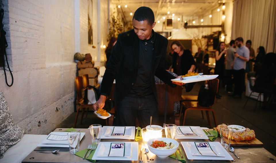 Boubacar Diallo serves food he prepared at an event for Emma's