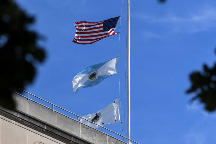 The flag for the Interior Department's deputy secretary, bottom, flies above agency headquarters in Washington. The mid