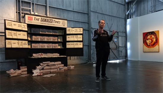 Shepard Fairey in front of The Damaged Times Newsstand installation; Background artwork - Media Target