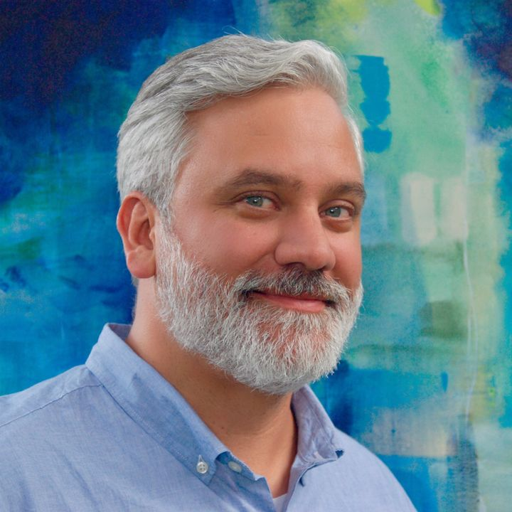 <p>Roger Hutchison stands in front of a painting from<em> My Favorite Color is Blue. Sometimes.</em></p>