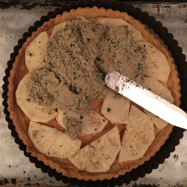 <p>Spread the onion-mushroom mixture over the celery root, filling in the gaps between pieces</p>
