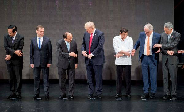 2. World leaders begin to take each other's hands. Trump turns to  Vietnam's Prime Minister Nguyen Xuan Phuc.