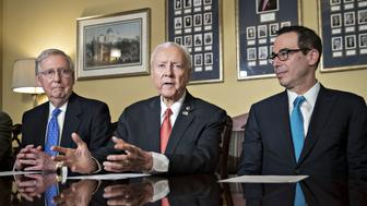 Senator Orrin Hatch, a Republican from Utah and chairman of the Senate Finance Committee, center, speaks as Steven Mnuchin, U.S. Treasury secretary, right, and Senate Majority Leader Mitch McConnell, a Republican from Kentucky, listen during a meeting with members of the committee on tax reform legislation at the U.S. Capitol in Washington, D.C., U.S., on Thursday, Nov. 9, 2017. Senate Republicans released their vision for a tax-cut plan Thursday that would cut the corporate tax rate to 20 percent, with a one-year delay to 2019, as Congress moves quickly to fulfill one of the GOPs biggest and most long-awaited goals. Photographer: Andrew Harrer/Bloomberg via Getty Images