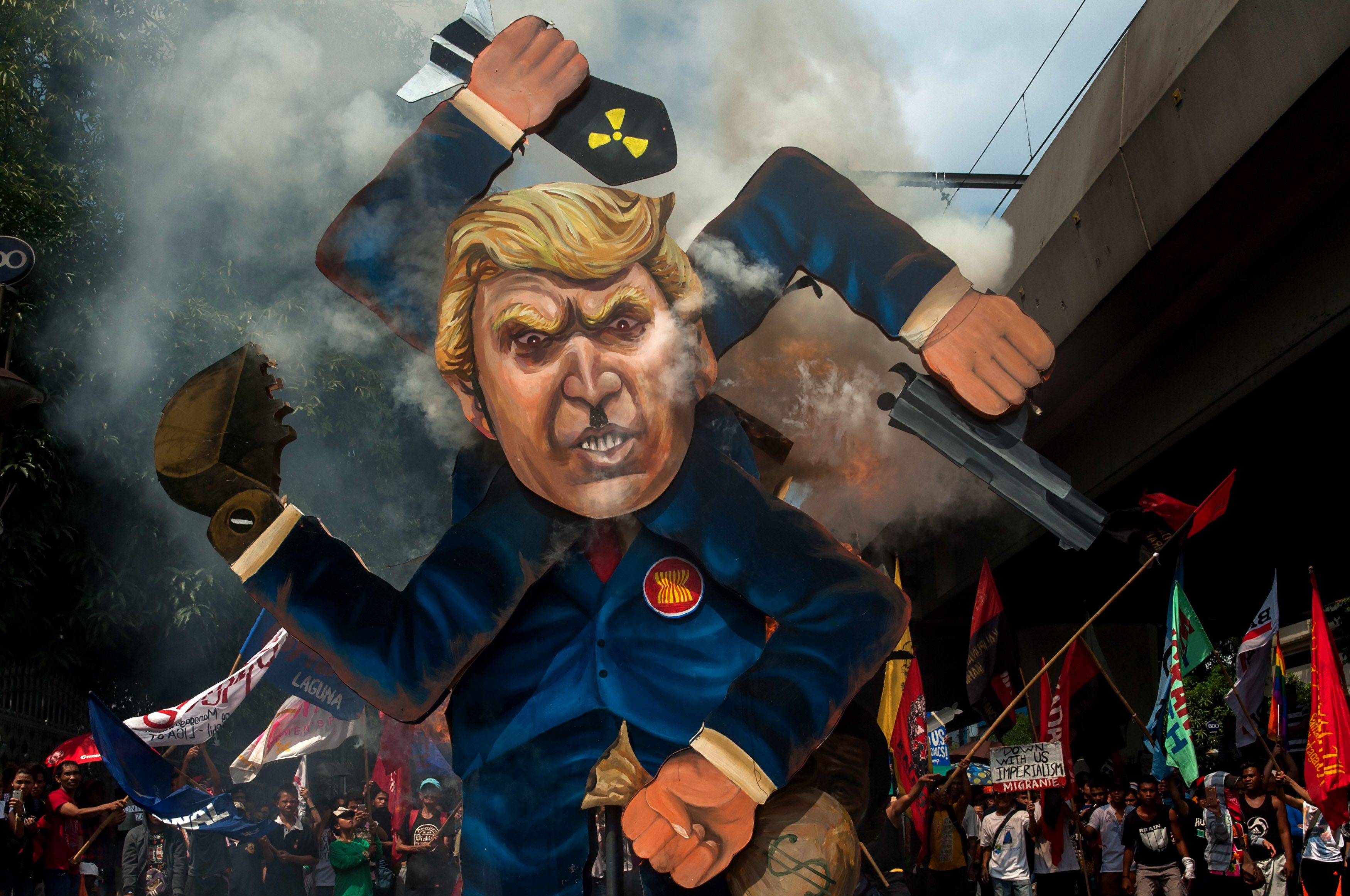 MANILA, PHILIPPINES - NOVEMBER 13: Protesters burn an image of US President Donald Trump fashioned on a swastika as they march the streets of Manila during the start of the ASEAN meetings between heads of state on November 13, 2017 in Manila, Philippines. Thousands of Filipinos protested in Manila as U.S. President Donald Trump's attended the ASEAN meetings in the Philippines, a stop included in his 12-day Asia trip.  (Photo by Jes Aznar/Getty Images)