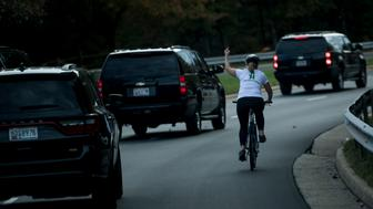 (FILES) This file photo taken on October 28, 2017 shows a woman on a bike gestures with her middle finger as a motorcade with US President Donald Trump departs Trump National Golf Course in Sterling, Virginia. Juli Briskman didn't think twice when she gave President Donald Trump the finger as his motorcade passed her while she was cycling on a road near his golf club. But the obscene gesture, captured on October 28 by AFP White House photographer Brendan Smialowski, who was riding in Trump's convoy, quickly went viral. And it has now cost the single mom her job. / AFP PHOTO / Brendan Smialowski