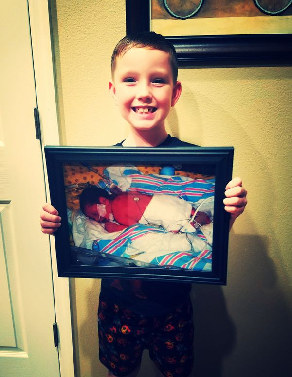 This is Landon, and he's holding a picture of himself from the day he was born. He was born more than eight weeks premature a