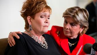 Attorney Gloria Allred (R) hugs Beverly Young Nelson as she reacts during a press conference on November 13, 2017, in New York, alledging that Roy Moore sexually assaulted Nelson when she was a minor in Alabama without her consent. The US Senate's top Republican on Monday urged scandal-hit conservative Roy Moore to end his Senate campaign,  saying he believes the women who have accused the Christian evangelical candidate of sexual misconduct. / AFP PHOTO / EDUARDO MUNOZ ALVAREZ        (Photo credit should read EDUARDO MUNOZ ALVAREZ/AFP/Getty Images)