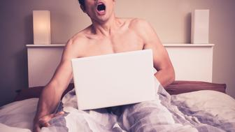 Young naked man is sitting in a bed and watching pornography on his laptop