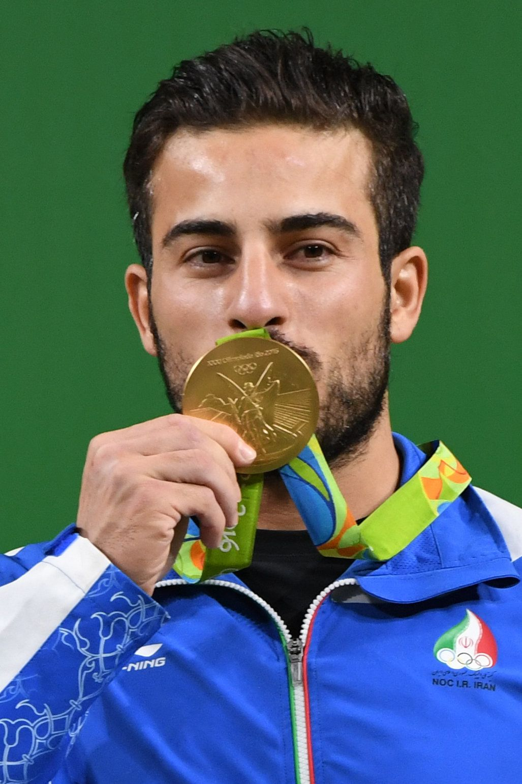 Iran's gold medallist Kianoush Rostami poses on the podium after the men's weightlifting 85kg event during the Rio 2016 Olympics Games in Rio de Janeiro on August 12, 2016. / AFP / GOH Chai Hin        (Photo credit should read GOH CHAI HIN/AFP/Getty Images)