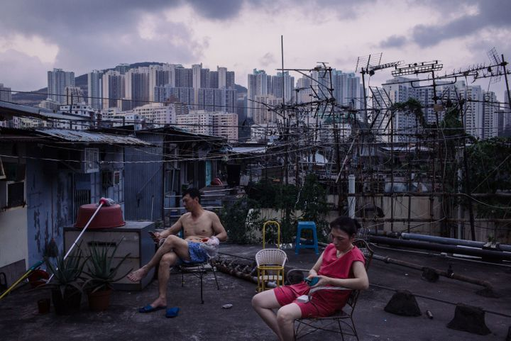 Migrant workers take a break after dinner outside a rooftop hut on June 3, 2017, in Hong Kong. Inequality has been on th