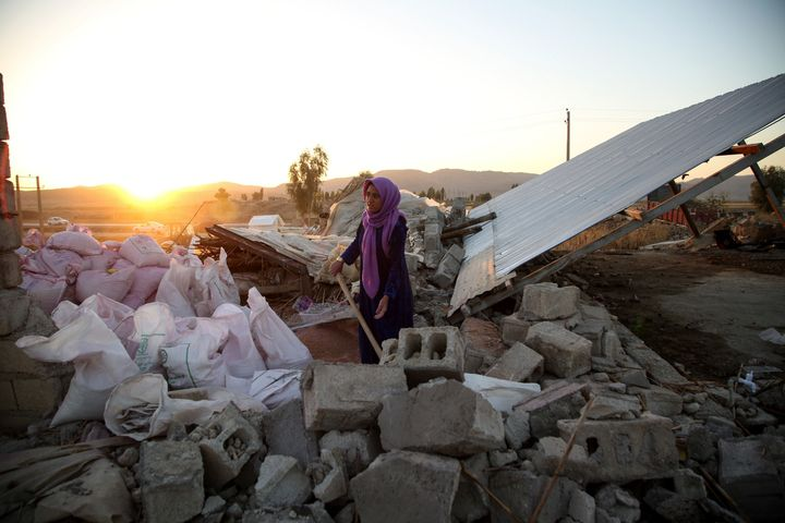 A woman struggles through the debris of a building in Kalaleh, Iran, on Tuesday,after a7.3-magnitude earthquake S