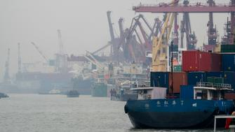NANTONG, JIANGSU, CHINA - 2017/11/13: Cranes are discharging containers from a cargo ship at Nantong Port.  As a big country of container manufacturing, China's great output has brought huge VOCs emissions. To solve the VOCs pollution problem, China will soon introduce the national standard for controlling the air pollutant emission in this industry. (Photo by Zhang Peng/LightRocket via Getty Images)