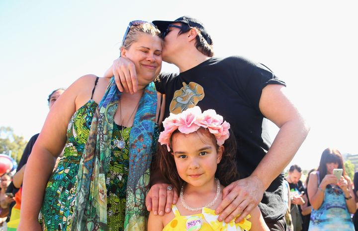 Mathilda Bowman, 5, looks on as her mothers, Kate Bowman and Melinda Voigt, each place a hand on her shoulder in Sydney.