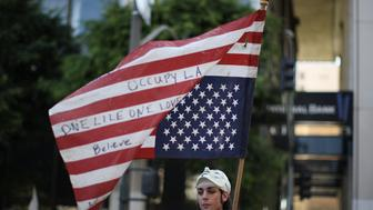 LOS ANGELES, CA - OCTOBER 1:  A protester holds an American flag during rally in the downtown financial district to mark the one-year anniversary of the Occupy movement on October 1, 2012 in Los Angeles, California. Inspired by Occupy Wall Street movement protests in New York, hundreds of Los Angeles demonstrators seized City Hall park last year and lived there for weeks until they were evicted in a dramatic police raid on the night of November 30, 2011.     (Photo by David McNew/Getty Images)