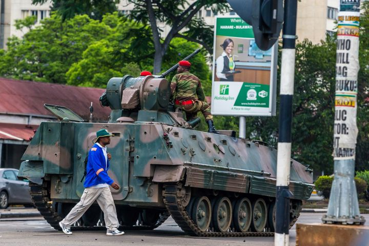 A man walks past an armored personnel carrier stationed at an intersection in Harare as Zimbabwean soldiers regulate tra