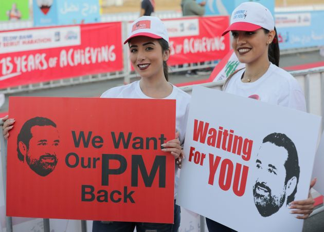 Hariri supporters at Beirut's annual marathon on Sunday hold up signs seeking his return to