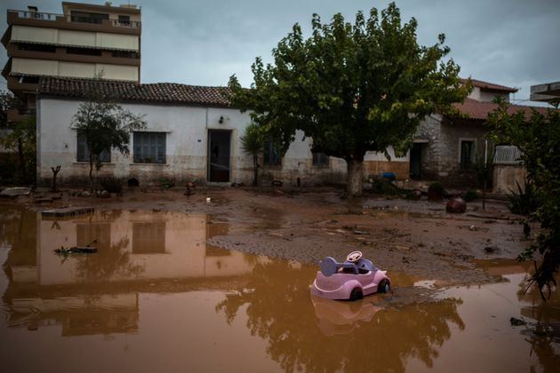 A toy car is seen in a flooded street next to a damaged house in the town of