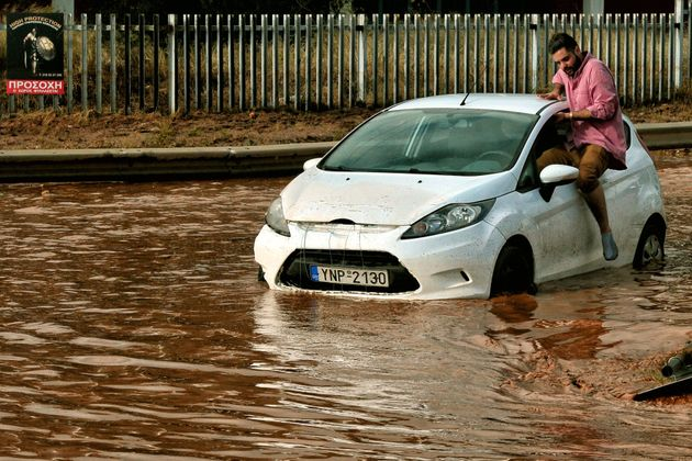 A man tries to get into a car stuck in floodwater in the town of