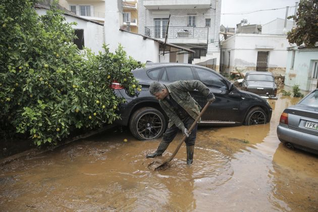 A man tries to remove floodwater from the area after torrential
