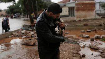A local, carrying a dog in his jacket, holds a cat he saved from a tree, following a heavy rainfall in the town of Mandra, Greece, November 15, 2017. REUTERS/Alkis Konstantinidis