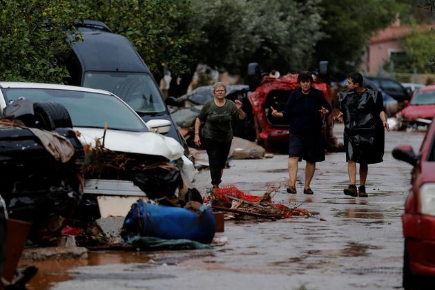 Locals walk next to destroyed cars following heavy