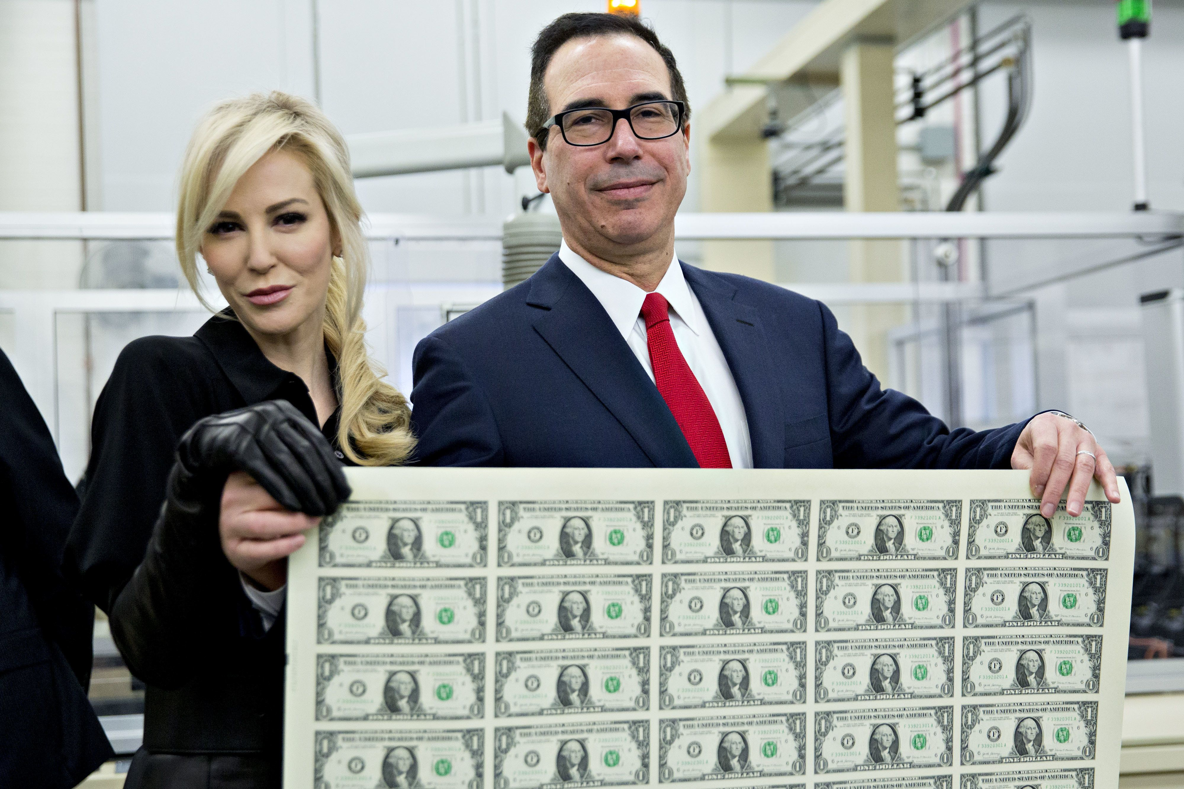 Treasury Secretary Steven Mnuchin and his wife, Louise Linton,pose on Wednesday holding a sheet of 50 $1bills bea