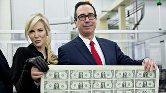 Steven Mnuchin, U.S. Treasury secretary, right, and his wife Louise Linton hold a 2017 50 subject uncut sheet of $1 dollar notes bearing Mnuchin's name for a photograph at the U.S. Bureau of Engraving and Printing in Washington, D.C., U.S., on Wednesday, Nov. 15, 2017. A change in the Senate tax-overhaul plan that would expand a temporary income-tax break for partnerships, limited liability companies and other so-called 'pass-through' businesses won the endorsement of a national small-business group today. Photographer: Andrew Harrer/Bloomberg via Getty Images