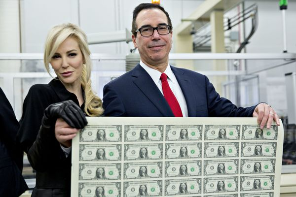 Treasury Secretary Steven Mnuchin and his wife, Louise Linton, pose on Wednesday holding a sheet of 50 $1 bills bea