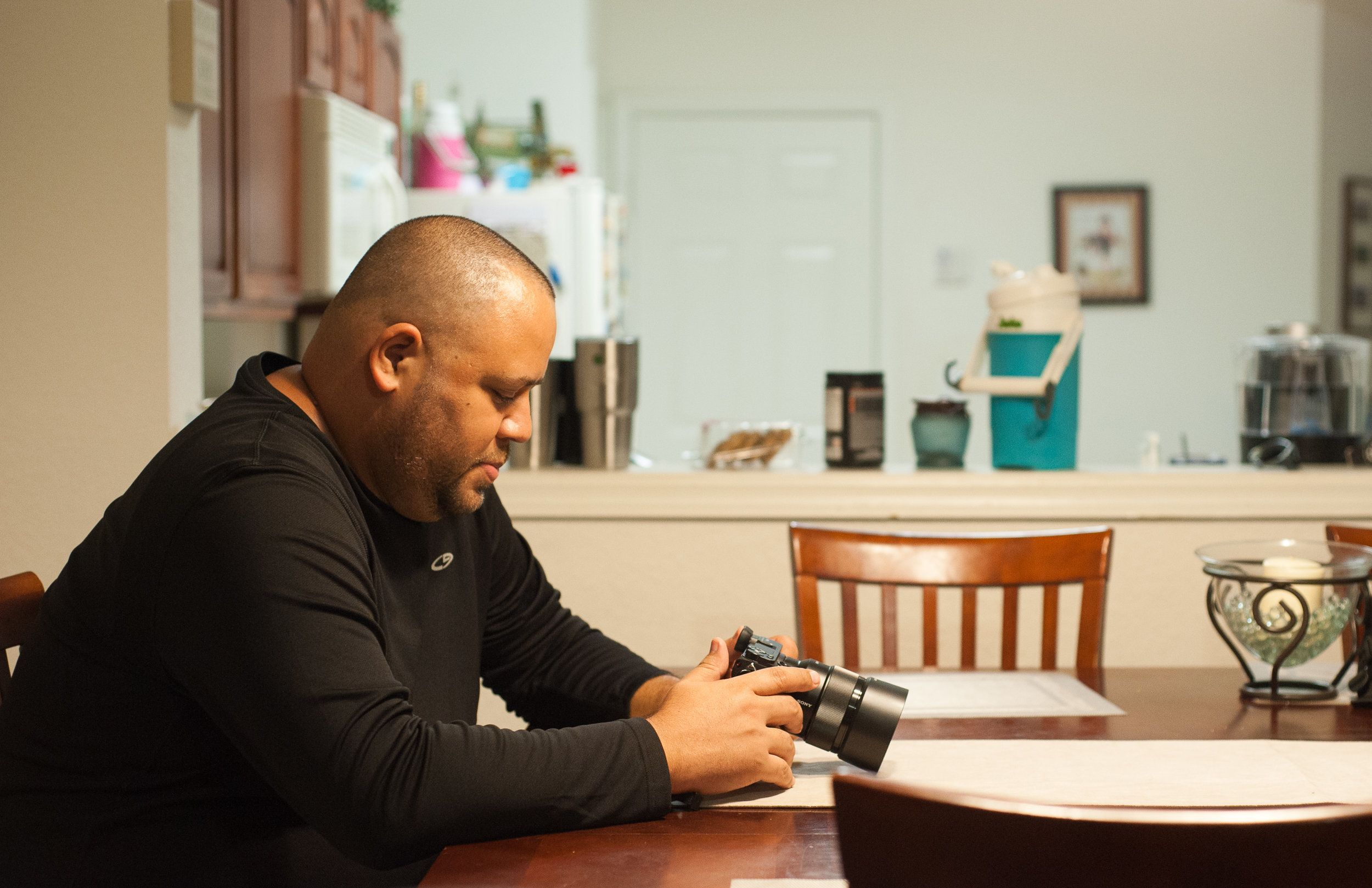 Delgado, in his home, looks at his camera. He took up photography after the Pulse shooting as a way to cope with his PTSD.