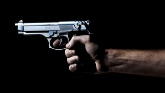 .40 caliber hand gun being shot in the dark, isolated on black.