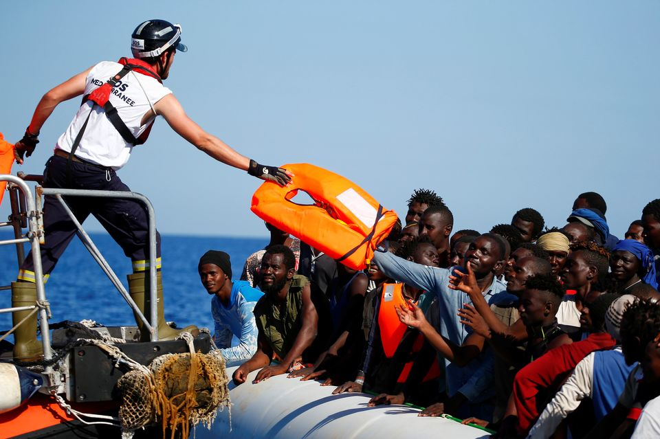 Migrants on a rubber boat are rescued by the SOS Mediterranee organization during a search-and-rescue...