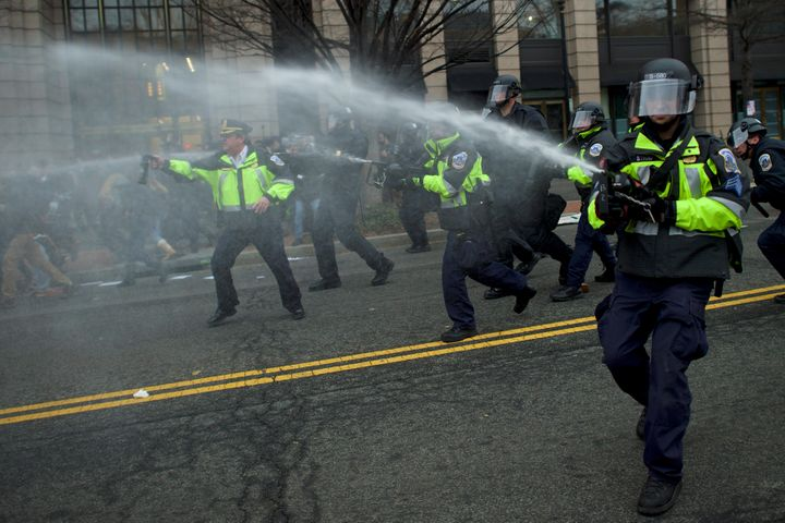 Police dispense pepper spray after a limousine was set on fire during the protests.
