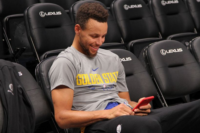 Stephen Curry laughs while looking at his phone following morning shoot around.
