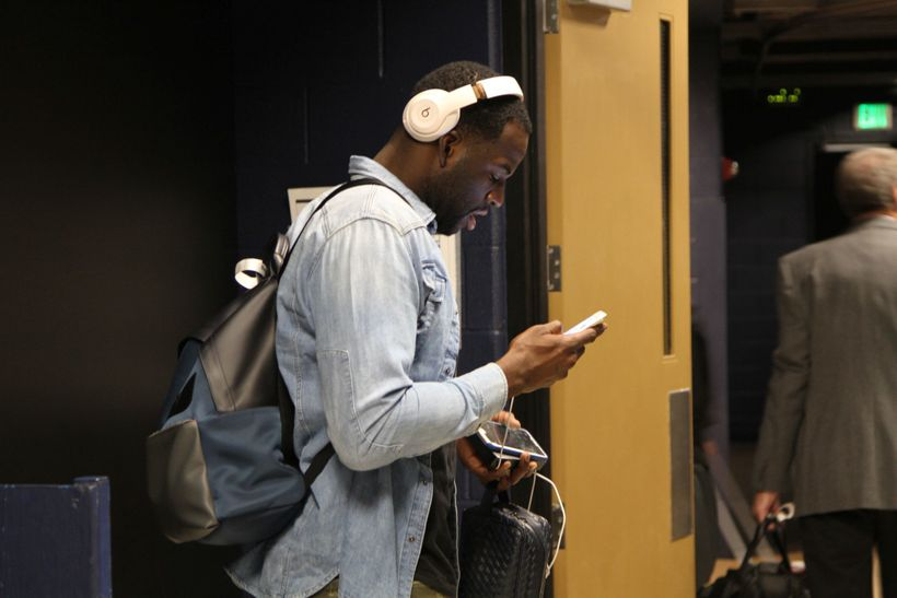Draymond Green looks at his phone at he walks through the team tunnel at the Pepsi Center prior to the start of the game.