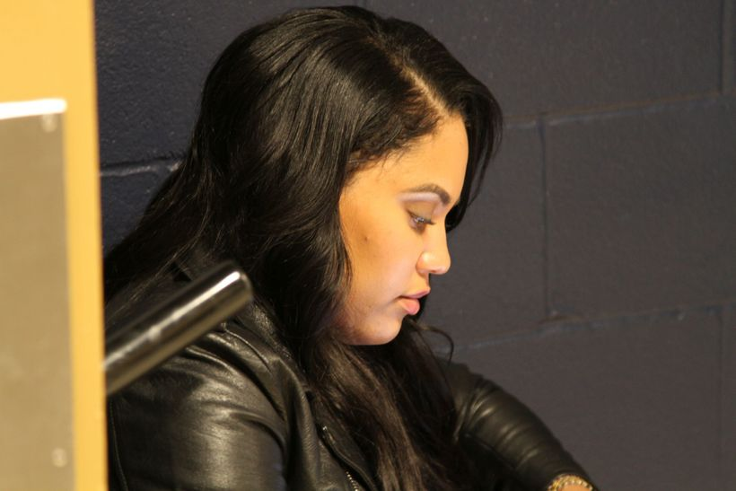 Ayesha Curry looks at her phone while waiting for her husband Stephen Curry outside the team locker room following the Warrio
