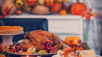 Table is set up for celebrating Thanksgiving. On the table is a traditional roasted turkey with side dishes and autumn decoration