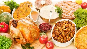 Subject: A Thanksgiving dinner with roast turkey and all the accompaniments such as cranberry sauce, stuffing, gravy, mashed potatoes, squash, green beans, sweet potatoes and apples. Photographed at an overhead high angle, looking down at the prepared, cooked food.