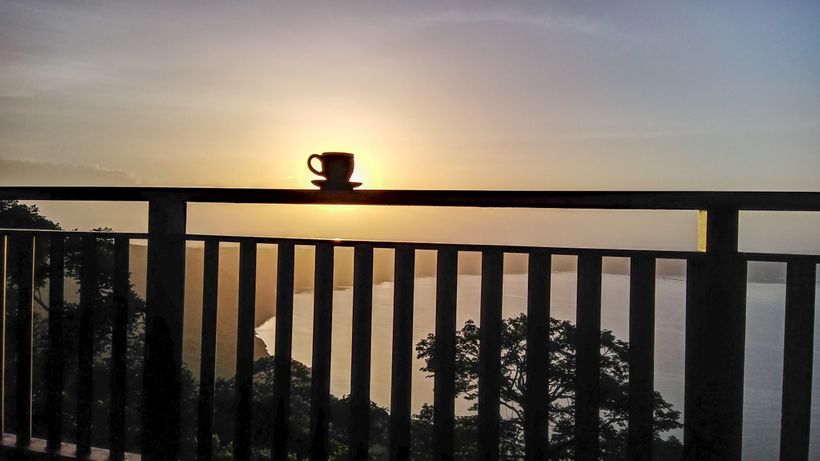 <em>Cafecito and a volcano lagoon sunrise, from Pacaya Lodge, on the crater above Laguna de Apoyo, Nicaragua.</em>