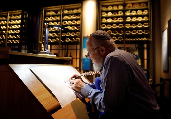 With ancient scrolls as a backdrop, Israeli Eliezer Adam works with ink and feather copying the Five Books of Moses, which he