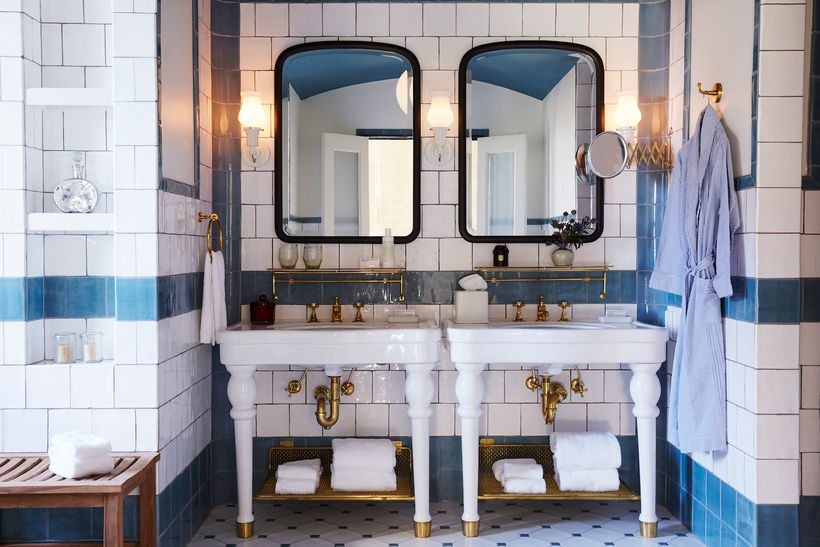 Custom tiles by Roman and Williams cover the walls of each guest bath.